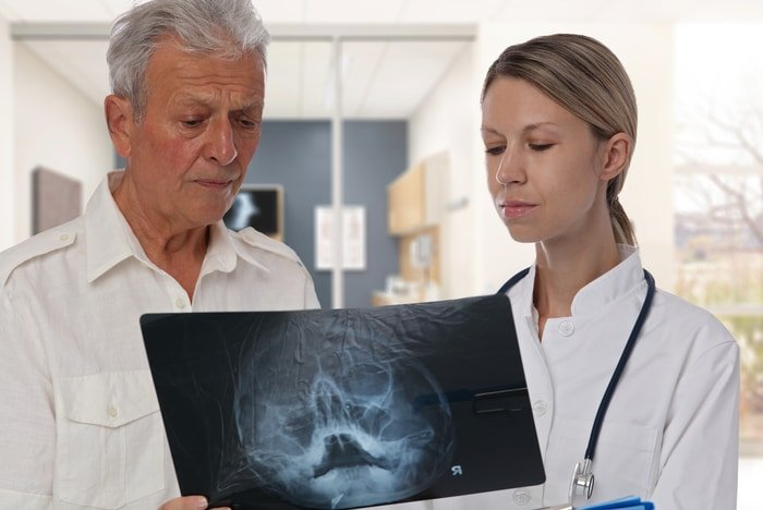 Patient and doctor reviewing xray - critical role of portable suction machine in dental trauma