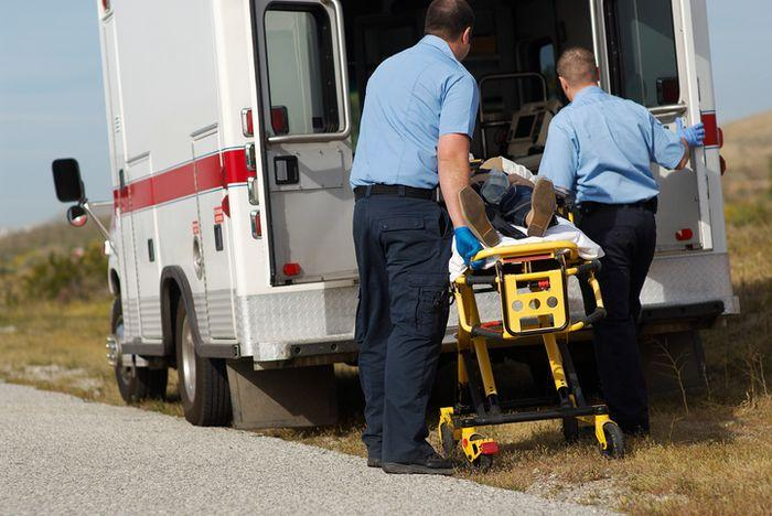 Two EMTs putting a patient into ambulance   why include a portable suction pump in your pedi bag?