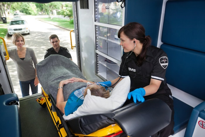 Paramedic treating patient on stretcher in an ambulance