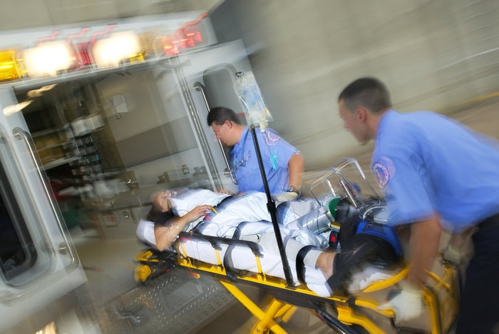 Paramedics putting a patient into an ambulance - how pharyngeal suction can save your patient