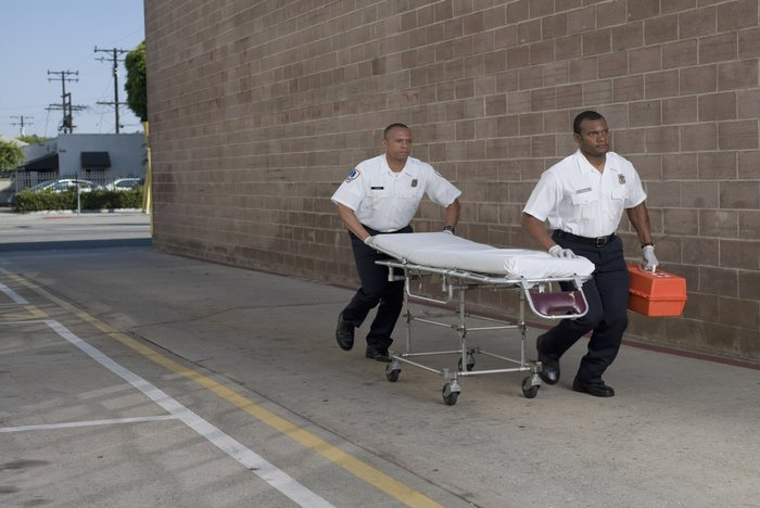 Paramedics rushing to scene with stretcher and respiratory emergency devices
