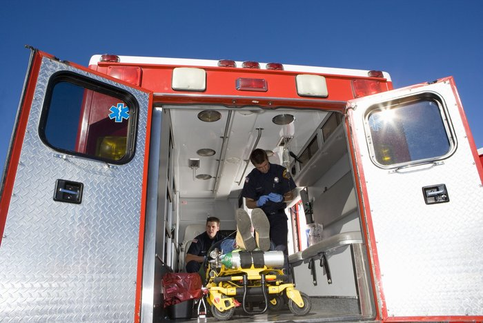 Patient being treated in ambulance - portable suction unit