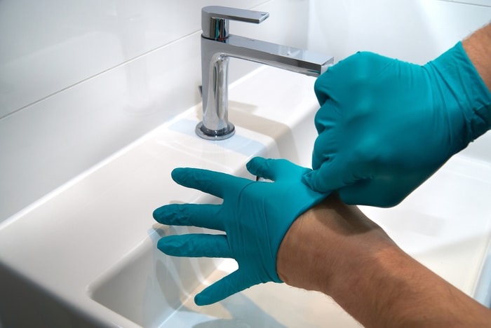 Washing hands while removing gloves - keeping your portable medical suction unit healthy